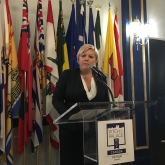 2019-april-tina-at-podium-with-flags.jpg
